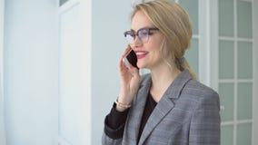 Ung kvinna i ett grått omslag som talar på le för telefon stock video