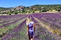 Ung kvinna i ett purpurfärgat lavendelfält royaltyfri foto