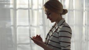 Ung kvinna i ett randigt omslag med en telefon på fönsterbakgrunden Royaltyfri Fotografi