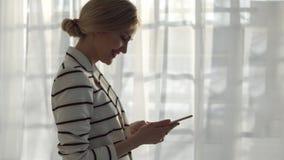 Ung kvinna i ett randigt omslag med en telefon på fönsterbakgrunden Royaltyfri Bild