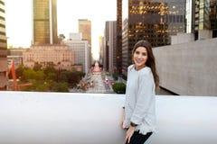 Ung kvinna i ett stads- landskap på solnedgången royaltyfria foton