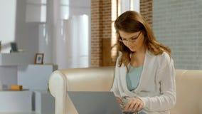 Ung kvinna i exponeringsglasarbete på den hemmastadda bärbara datorn, dålig synförmåga, frilans royaltyfria bilder