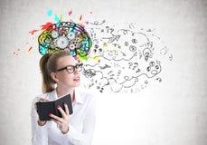 Ung kvinna i exponeringsglasatt skriva, hjärna och pilar Royaltyfri Bild