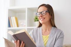 Ung kvinna i exponeringsglasläsebok hemma Royaltyfria Foton