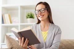 Ung kvinna i exponeringsglasläsebok hemma Arkivbild