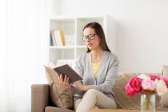Ung kvinna i exponeringsglasläsebok hemma Royaltyfria Bilder