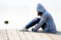 Ung kvinna i förtvivlan som sitter nära floden fotografering för bildbyråer