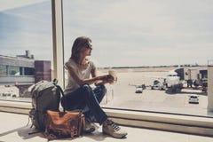 Ung kvinna i flygplatsen som ser till och med fönstret på nivåer och dricker kaffe, lopp, semestrar och aktiv livsstilconce royaltyfri bild