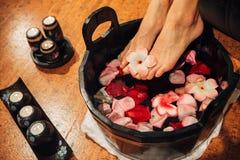 Ung kvinna i fot-bad i orientaliskt örtvatten för kroppdetox Arkivfoton