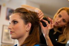 Ung kvinna i frisörsalongen som har en behandling och en frisyr Arkivfoton