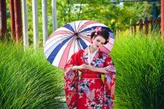 Ung kvinna i geishadräkt med ett paraply Royaltyfria Bilder