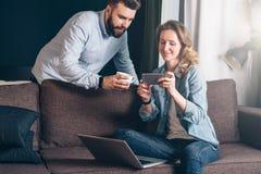 Ung kvinna i grov bomullstvillskjortan som hemma sitter på soffan och använder bärbara datorn Närliggande ställningsman och se på Arkivfoton