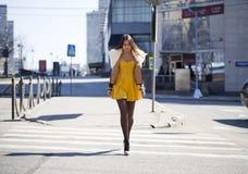 Ung kvinna i gul klänning som utanför korsar vägen fotografering för bildbyråer