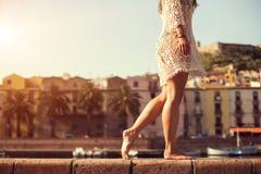 Ung kvinna i gullig sommarklänning som går på solnedgången Arkivbilder