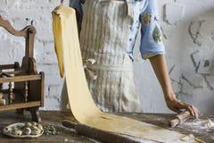 Ung kvinna i hållande deg för förkläde för hemlagad pasta arkivbild