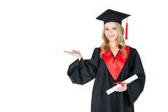 Ung kvinna i hållande diplom för akademikermössa och visningkopieringsutrymme Fotografering för Bildbyråer