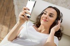 Ung kvinna i hörlurar genom att använda smartphonen, medan ligga på soffan Royaltyfria Bilder