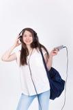 Ung kvinna i hörlurar som sjunger sånger på en vit bakgrund Arkivfoto