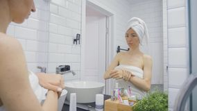 Ung kvinna i handduken som applicerar kr?m f?r att v?nda mot och ser f?r att avspegla det hemmastadda badrummet Sk?nhet livsstil, stock video