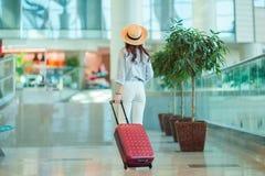 Ung kvinna i hatt med bagage i internationell flygplats Flygbolagpassagerare i ett väntande på flyg för flygplatsvardagsrum Arkivbild
