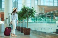 Ung kvinna i hatt med bagage i internationell flygplats Flygbolagpassagerare i ett väntande på flyg för flygplatsvardagsrum Royaltyfri Bild