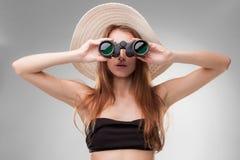 Ung kvinna i hatt med kikare Arkivfoto