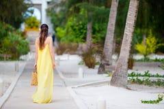 Ung kvinna i hatt under tropisk strandsemester Tillbaka sikt av den lyckliga flickan som tycker om henne ferier Fotografering för Bildbyråer