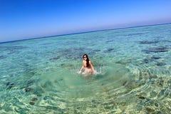Ung kvinna i havet Arkivbild