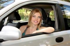 Ung kvinna i henne ny bil Arkivbild