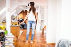 Ung kvinna i hennes lägenhet, genom att använda Vr exponeringsglas Arkivbilder
