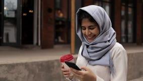 Ung kvinna i hijab som dricker ett kaffe för att gå se smartphonen lager videofilmer