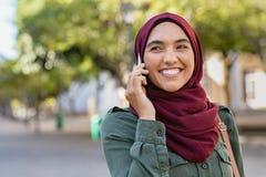 Ung kvinna i hijab som talar på telefonen arkivfoton