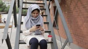 Ung kvinna i hijabsammanträde på yttersida och att smsa för trappa lager videofilmer