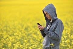 Ung kvinna i hoodien som smsar ett meddelande på hennes smarta telefon Fotografering för Bildbyråer