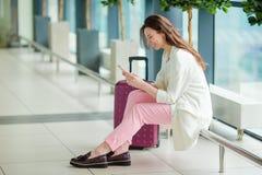 Ung kvinna i internationell flygplats med hennes bagage och smartphone som väntar på hennes flyg Arkivfoton