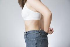 Ung kvinna i jeans av det stora formatet, begrepp av viktförlust Royaltyfri Fotografi