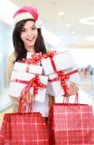 Ung kvinna i julhatt/santa med den shoppingpåsar och gåvan Royaltyfria Foton