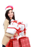 Ung kvinna i julhatt/santa med den shoppingpåsar och gåvan Arkivfoto