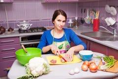 Ung kvinna i kök fotografering för bildbyråer