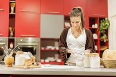 Ung kvinna i köket Arkivfoto