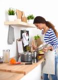 Ung kvinna i köket som förbereder en mat Arkivbilder
