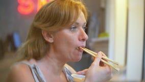 Ung kvinna i kafé som äter sushi med pinnar 4k närbild stock video