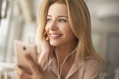 Ung kvinna i kafésammanträde som lyssnar till musik som ut ser den dreamful närbilden för fönster Arkivbilder