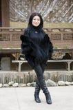 Ung kvinna i kläder av mörk päls som framme står av det koreanska lilla huset. Fotografering för Bildbyråer