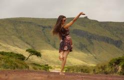 Ung kvinna i klänning med det lyftta enkla trädet för handneare på vägen Arkivfoton