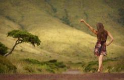 Ung kvinna i klänning med det lyftta enkla trädet för handneare på vägen Royaltyfri Bild