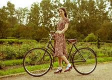 Ung kvinna i klänningen som poserar med den retro cykeln i parkera. arkivbild