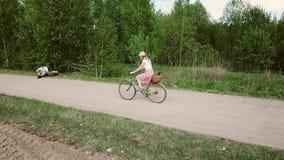 Ung kvinna i klänningritter en cykel arkivfilmer