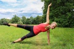 Ung kvinna i konditionövning med ett ben upp Arkivbilder