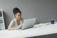 Ung kvinna i kontoret Arkivbild